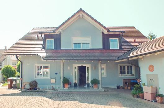 """Der Eingangsbereich dieses Wohnhauses in Freiburg Munzingen lebt mit und von der darüber liegenden Dachgaube. Die Kombination aus Sattelgaube und Schleppgaube in Verbindung mit den Eingangssäulen hat etwas von """"Märchenschloss"""""""