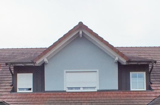 """Der Eingangsbereich dieses Einfamilienhauses in Freiburg Munzingen lebt mit und von der darüber liegenden Dachgaube. Die Kombination aus Sattelgaube und Schleppgaube in Verbindung mit den Eingangssäulen hat etwas von """"Märchenschloss"""""""